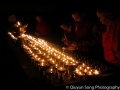 Bhutanese monks lighting candles before dawn at the final day of the Paro Tsechu Festival