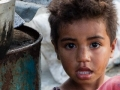 Beautiful girl standing by her mother's roadside stall in Fiji